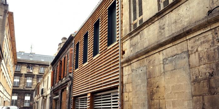Habitat partagé à Bordeaux : Une façade en bois dans une rue en pierre